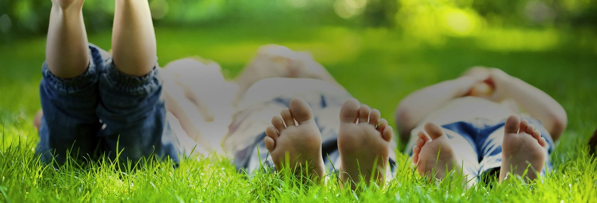 three kids laying in grass treated by natural green because it is non toxic